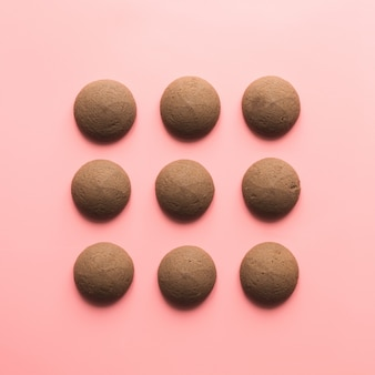 Nine cookies in row in pink surface