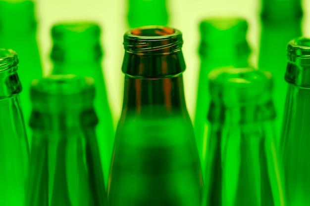 9本の緑と1本の茶色のボトルが緑色の光で撮影されました。中央の茶色のボトルネックに焦点が当てられています。