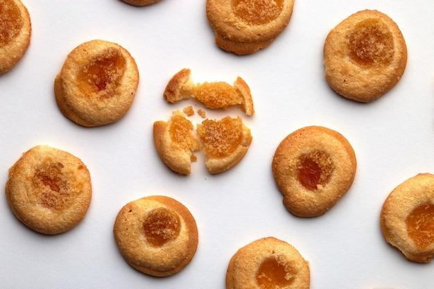 살구 잼을 곁들인 수제 쿠키 9 개가 비스듬히 균등하게 배열되어 있습니다. 흰색 배경에 고립
