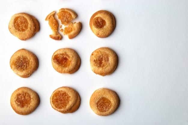 살구 잼을 곁들인 수제 쿠키 9 개가 여유 공간이 균등하게 배열되어 있습니다.
