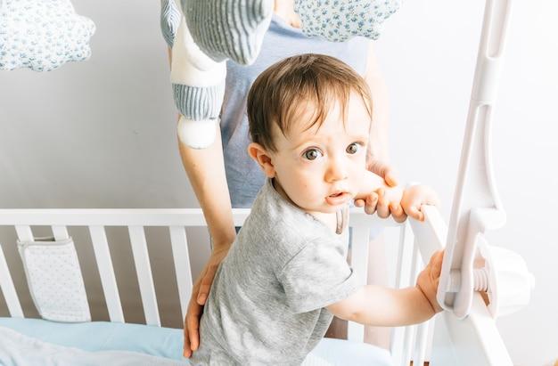 母親と一緒にベビーベッドで遊んでいる生後9か月の赤ちゃん。彼女のコンセプトの赤ちゃんと母親。マタニティ