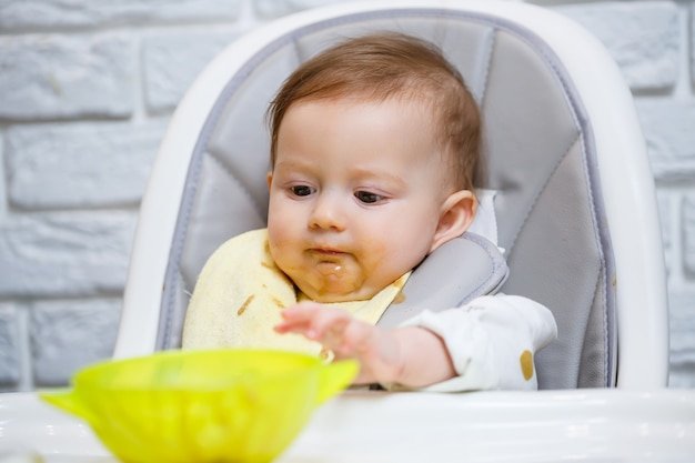 A nine month old smiling baby sits at a white table in a highchair and eats with a spoon from a bowl. mom feeds the baby from a spoon. blurred background. healthy food for children. children food.