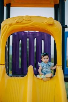 Девять месяцев очаровательная няня сидит и позирует на желтой горке на детской площадке