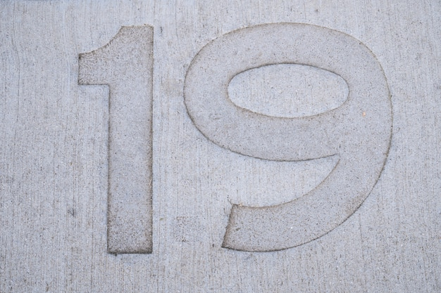Nineteen (19) number stamped on concrete floor.
