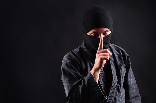 Ниндзя в балаклаве на темноте держит указательный палец на губах.