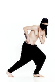 Человек-ниндзя держит нож и готов атаковать на белом фоне