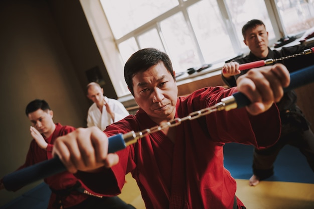Ninja man in a red kimono holding a nunchuck in his hands.