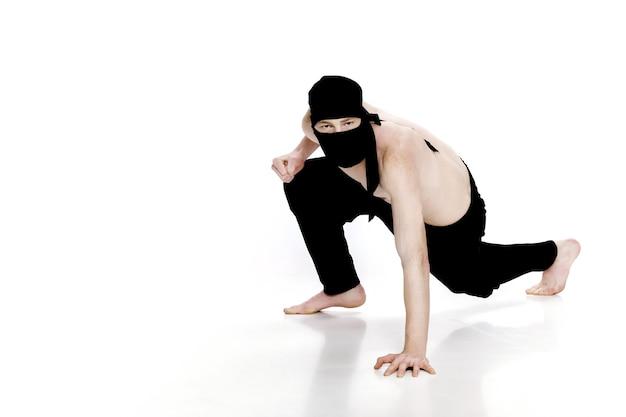 Ниндзя на белом фоне мужчина-боец в черной одежде