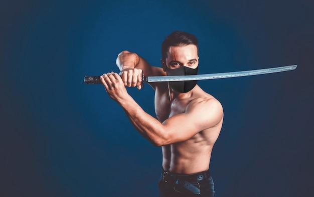 Воин-самурай ниндзя в маске с обнаженным торсом в позе атаки с мечом катана