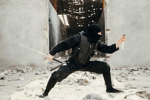 Воин ниндзя показывает трюки в черных нарядах, держа печаль
