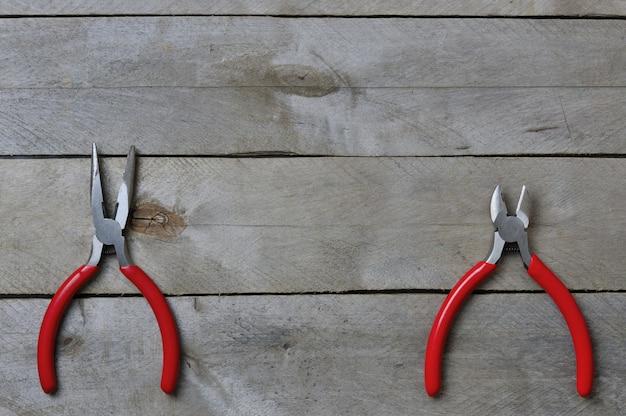 木製の背景に赤いハンドルが付いているニッパーとペンチ。コピースペース。