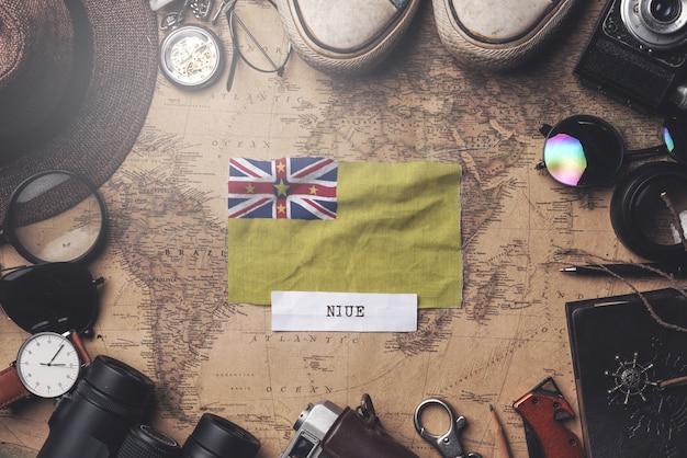 Флаг ниуэ между аксессуарами путешественника на старой винтажной карте. верхний выстрел