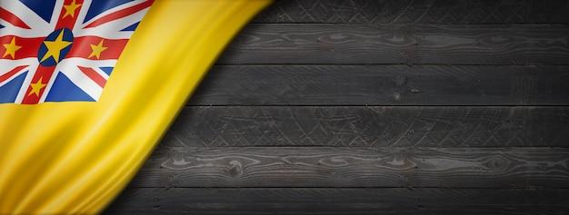 검은 나무 벽에 니우에 플래그입니다. 수평 파노라마 배너.
