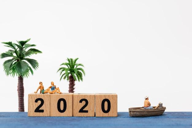 Миниатюрные люди в купальниках отдыхают сидя на деревянном блоке № 2020