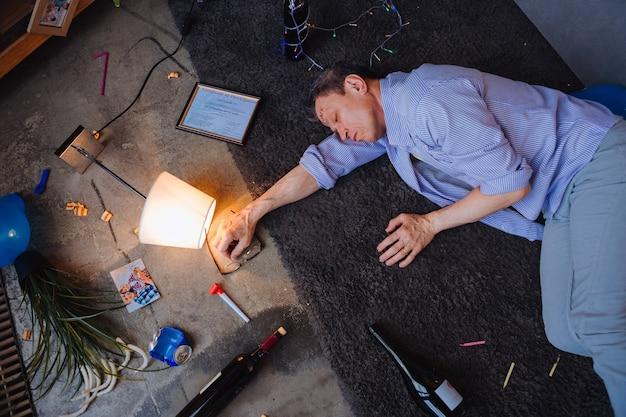 Без ограничений по алкоголю. спокойный зрелый мужчина лежит на полу и видит сны