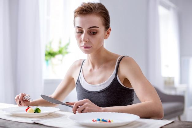 食欲はありません。丸薬を見ながら食べ物を食べようとしている落ち込んでいる若い女性