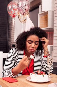 Нет аппетита. грустная несчастная женщина смотрит на кусок торта без аппетита