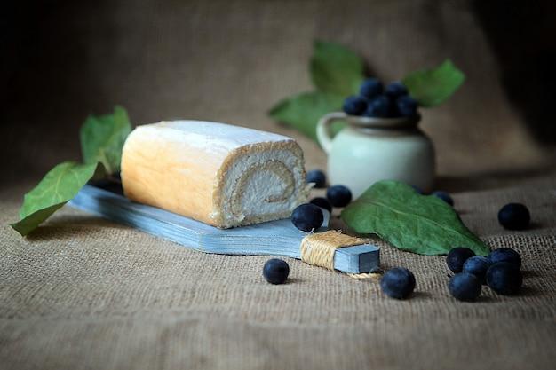 코코넛 크림과 자두로 속을 채운 노베이크 커드 롤 케이크, 소박한 스타일.