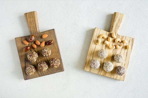 Не испечь энергетические шары сладостей с фундуком, кешью, арахисовым маслом и миндалем на деревянных досках на белом фоне. органические закуски. вид сверху, крупным планом.