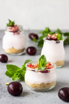 No baked cheesecake with cherry in glass jars, fresh cherries and mint on a grey stone