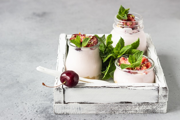 No baked cheesecake with cherry in glass jars, fresh cherries and mint. healthy dessert.