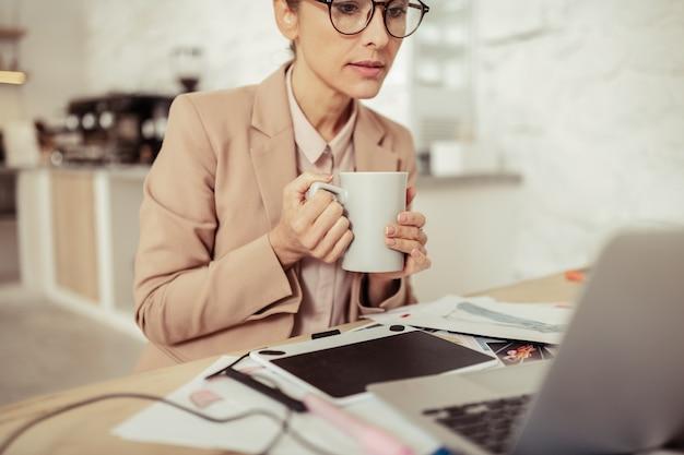 休憩なし。ノートパソコンでの作業中にコーヒーを持っている美しい眼鏡をかけた女性。