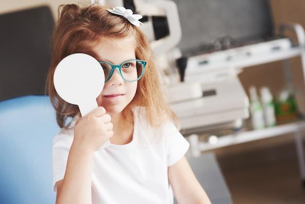 Никакого обмана, мы хотим, чтобы этот тест прошел правильно. маленькая девочка проверяет его зрение в новых зеленых очках.