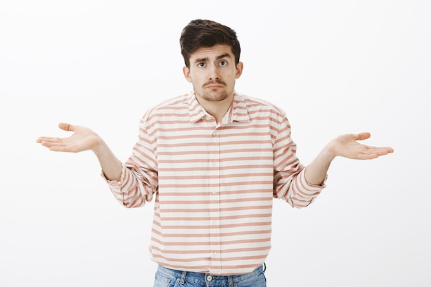 No clue, no guesses. portrait of gloomy unsure boyfriend with moustache, shrugging with spread palms, being confused and unaware what is happening, standing clueless