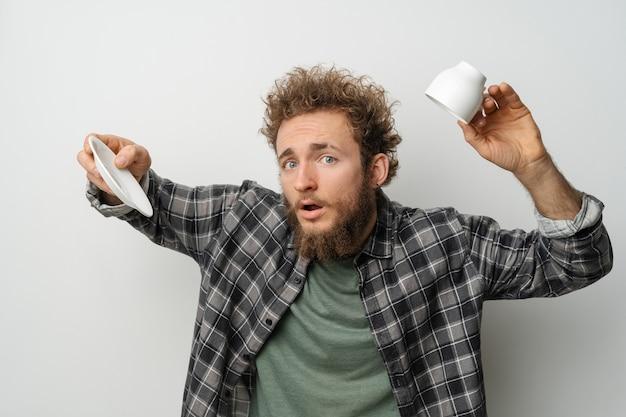白い壁に隔離された格子縞の長袖シャツを着て、巻き毛とひげ保持カップを持つ逆さまのカップの格好良い男にコーヒーはありません