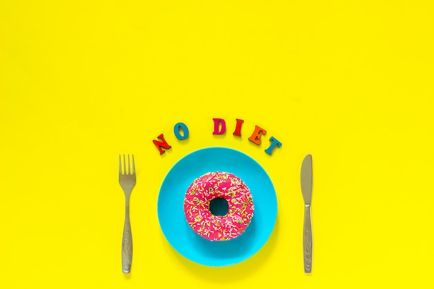 No diet and pink donut on blue plate and knife fork on yellow background.