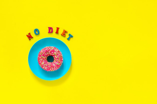 No diet and pink donut on blue plate on yellow