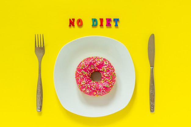 No diet and pink donut on white plate and knife fork on yellow background.