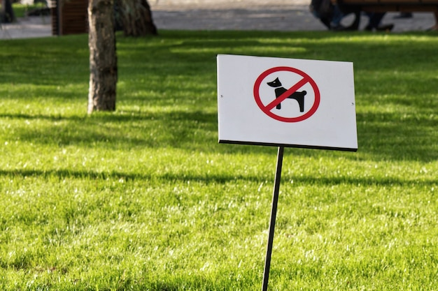 Знак запрета собак в парке с зеленой травой на заднем плане