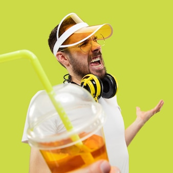 間違いなく、さあ。シャツを着た若い男のハーフレングスのクローズアップの肖像画。ヘッドフォンと飲み物を持つ男性モデル。人間の感情、表情、夏、週末のコンセプト。