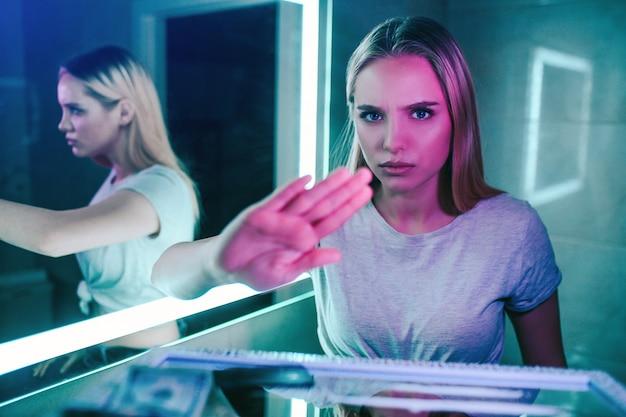 Нет наркотиков концепции. отклонить предложение наркотиков. рука говорит нет. молодая женщина показывает открытую ладонь против предложения наркотиков в туалете ночного клуба. прекратить наркоманию.