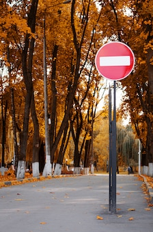 No entry road sign in autumn park. fall season. vertical