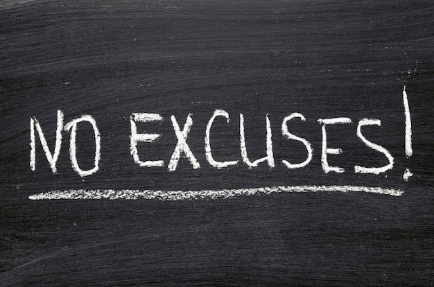 No excuses phrase handwritten on blackboard