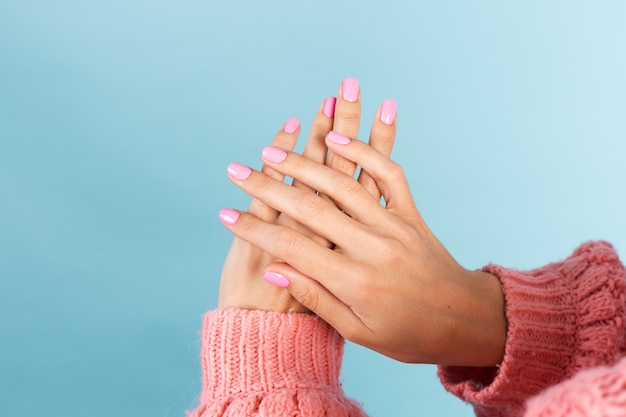 No face photo of womans  hands with bright pink nail color manicure on wall