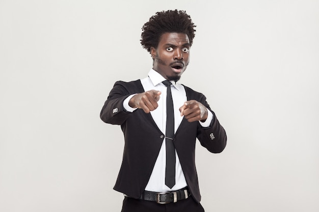 No fair! african man pointing fingers and shocked. studio shot, gray background