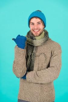독감이 없습니다. 겨울 일기예보. 남자는 따뜻한 옷을 입는다. 남성 니트 패션. 남자 니트 천 및 액세서리. 남성 파란색 배경입니다. 가난한 노숙자. 겨울에 추위를 느끼는 행복한 남자.