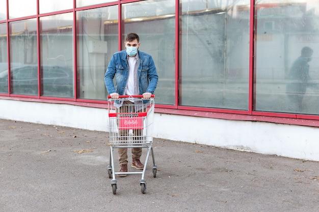 음식 문제 없음, 공황 구매 음식. 코로나 바이러스, 바이러스, 감염, 전염병, 전염병을 두려워하는 구매 빈 슈퍼마켓 트롤리가 달린 의료용 보호 마스크를 착용 한 사람. 유럽 eu의 새로운 코로나 바이러스