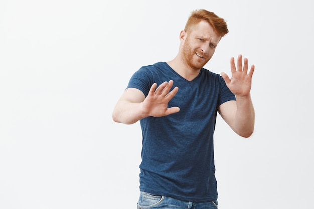 No go away from me. displeased uninterested picky redhead male entrepreneur in blue t-shirt, pulling hands in refusal gesture, frowning bothered, giving rejection, declining offer