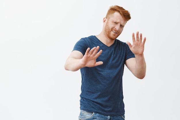 Не уходи от меня. недовольный равнодушный придирчивый рыжий предприниматель в синей футболке, тянущий за руки в жесте отказа, озабоченно хмурясь, отказываясь от предложения, отклоняя предложение