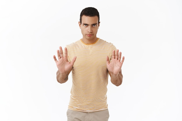 No, i dont want. serious-looking confident and determined hispanic young masculine man making stop gesture