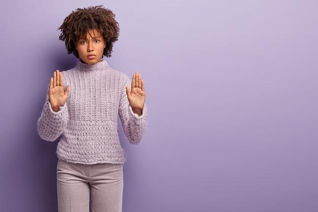いいえ、拒否します。美しい怒っている暗い肌の女性は手のひらを見せ、両手でジェスチャーを停止し、意見の相違を表現し、カジュアルなジャンパーを着て、紫色の壁の上に立って、スペースを右にコピーします