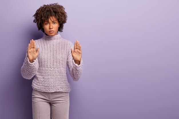 No, i refuse. beautiful angry dark skinned woman shows palms, makes stop gesture with both hands, expresses disagreement, wears casual jumper, stands over purple wall, copy space right