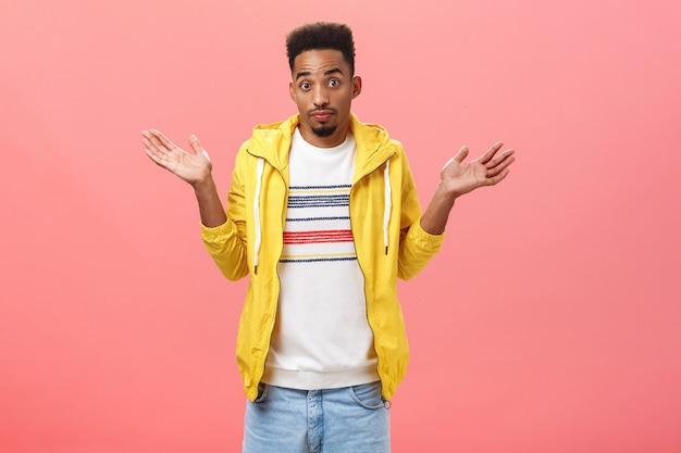아무 생각 없어 형. 턱수염과 아프로 헤어스타일을 한 확실하지 않은 아프리카계 미국인 남자는 분홍색 벽 너머로 불확실하고 인식하지 못하는 어깨 근처에 손바닥을 들고 어깨를 으쓱하는 노란색 트렌디한 재킷을 입고 있습니다.