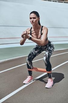 Никаких «если» или «но» перед тренировкой. красивая молодая женщина в спортивной одежде на корточках с помощью группы сопротивления