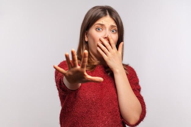 シャギーセーターのジェスチャーストップでパニックに陥った怖い女の子の肖像画を恐れていません