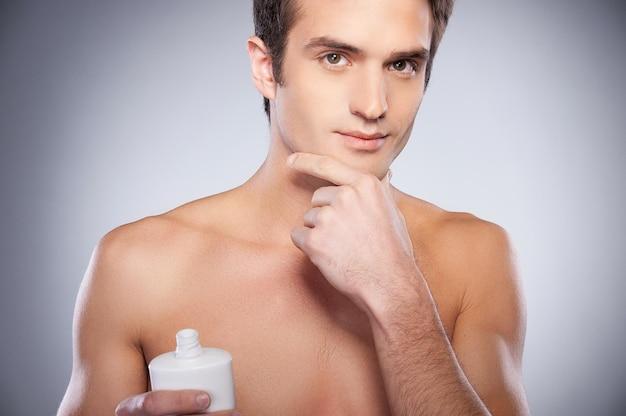Никакого раздражения. красивый молодой человек без рубашки, наносящий крем на лицо и смотрящий в камеру, стоя на сером фоне